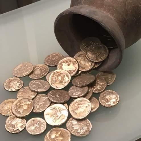 Primeras monedas acuñadas en la Península Ibérica. Monedas de plata, la mayoría en el anverso tienen la cabeza de la diosa Atenea y en el reverso una lechuza y letras EM.